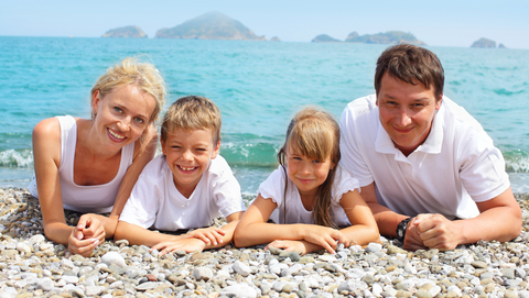 young healthy family lying on ocean beach facing viewer